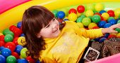 Preschooler girl with ball in play room. Childcare.