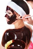 Beautiful girl  having  chocolate facial mask apply by  beautician. Isolated.