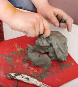 Child moulding from clay in play room. Body part.