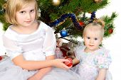 girl gives christmas ball her baby sister