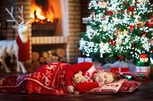 Child At Christmas Tree. Kid At Fireplace On Xmas poster