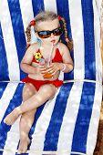 Little girl in glasses and red bikini drink orange juice.