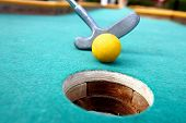 stock photo of miniature golf  - Golf stick and ball on green grass close up - JPG