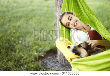 poster of Smiling Young Woman In Green Hammock With Cute Dog Welsh Corgi In A Park Outdoors. Beautiful Happy F