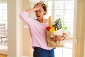 Young african american woman holding paper bag full of fresh groceries stressed with hand on head, s poster
