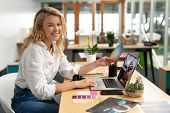 Portrait of Caucasian female graphic designer holding a color swatch while using laptop at desk in o poster