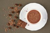 Above shot of cappuccino in porcelain cup strewed with grated chocolate, piece of chocolate and coffee grains near by