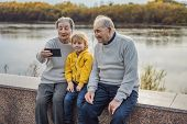 Senior Couple With Great-grandson Take A Selfie In The Autumn Park. Great-grandmother, Great-grandfa poster