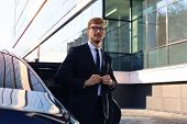 Handsome Serious Young Businessman Standing Near His Comfortable New Car And Going To The Office. poster