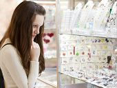 image of rapture  - Young woman is choosing jewerly in the shop - JPG