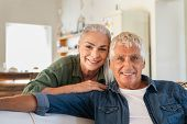 Portrait of happy senior couple relaxing at home and looking at camera. Romantic mature woman embrac poster