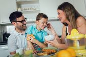 Family Eating Breakfast At Kitchen Table, Having Fun poster