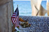 United States Flag, Flowers And Objects In Memory Of Fallen In Normandy Landing. Omaha Beach Memoria poster