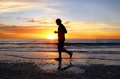 A Silhouette Of A Peaceful Young Man Exercising Alone On The Beach At Sunset. poster