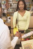 picture of grocery store  - African American woman at checkout counter in health food store - JPG