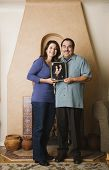 Hispanic couple holding their wedding photograph