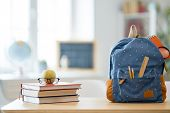 Back to school and happy time! Apple, pile of books and backpack on the desk at the elementary schoo poster