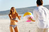 Casal jovem em umas férias de praia verão brincando com um beachball e divertir-se despreocupado