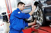 stock photo of garage  - car mechanic installing sensor during suspension adjustment and automobile wheel alignment work at repair service station - JPG