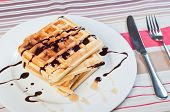 waffle with a drizzle of chocolate and caramel syrup