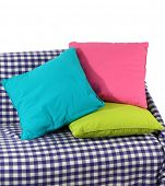 Colorful pillows on couch isolated on white
