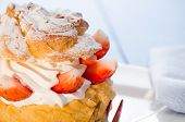 stock photo of cream puff  - fresh cream puff with whipped cream mint and strawberries on white plate and white wood table - JPG