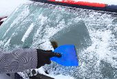 stock photo of scrape  - Hand scraping ice from the car window in winter time - JPG