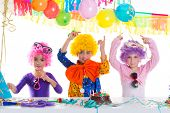 Children happy birthday party with clown wigs and chocolate cake