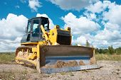track-type loader bulldozer excavator machine doing earthmoving work at sand quarry