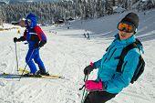 Esquiadores con cielos; chaqueta azul;  orientación horizontal