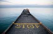 Pier Perspective With Yellow Stop-line And Stop Label On Black Sea Coast. Russia, Sochi, Adler