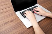 Close up of businesswoman's hands using laptop at table
