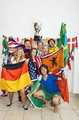Portrait of successful athletes with various national flags celebrating at home
