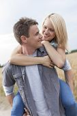 image of piggyback ride  - Romantic young man piggybacking woman on field - JPG