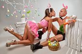 Lovely couple in rabbit costumes with carrots and eggs