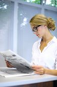 A serious girl with glasses reading a newspaper at the table in the library