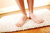 Piernas del hombre en una alfombra de baño