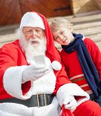 Santa Claus and boy taking selfportrait through smartphone outside house