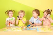 image of toy phone  - Two boys and two girls with phones in their hands are sitting at a table with toys - JPG