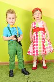 Boy with microphone and girl in bright clothes on a background of yellow green wall