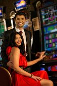 stock photo of gambler  - Beautiful young couple near slot machine in a casino - JPG