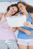 Smiling girls lying in bed wearing pajamas and holding tablet at sleepover