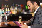 Close up of businessman sitting at bar and reading drinks menu