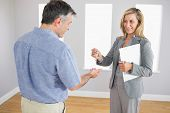 Pleased blonde realtor holding a briefcase and giving a key to a mature buyer in an empty room