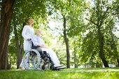 stock photo of wheelchair  - Pretty nurse walking with senior patient in a wheelchair in park - JPG