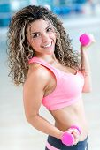 Happy woman lifting weights at the gym keeping fit