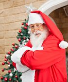 Portrait of senior man dressed as Santa Clause standing arms crossed outside house