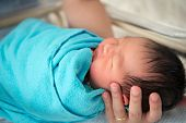 image of bassinet  - Father holding newborn Asian baby girl - JPG