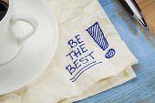 be the best  - motivational slogan on a napkin with cup of coffee
