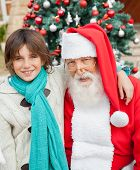 Portrait of happy boy with arm around Santa Claus against Christmas tree